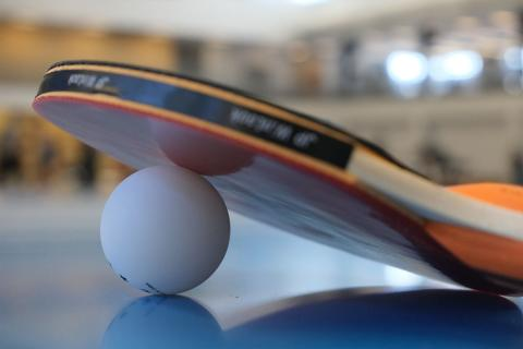 close up of table tennis paddle and ball