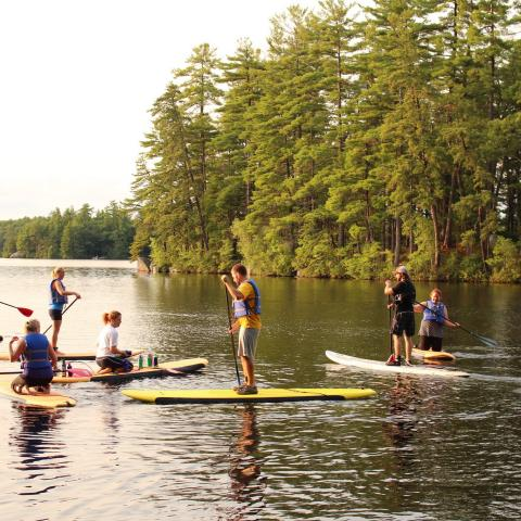 Students stand-up paddleboarding on Mendums Pond.